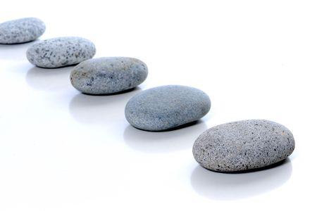 白の背景に一直線に並べられた石