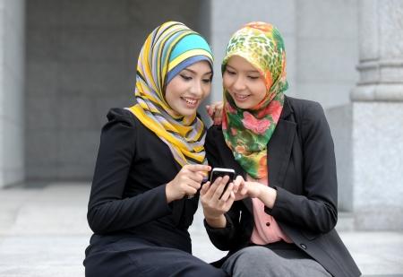 femme musulmane: Deux fille �charpe utiliser t�l�phone intelligent Banque d'images