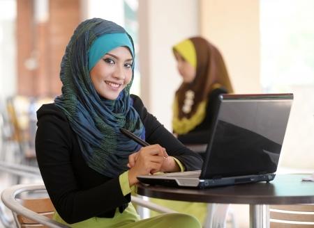 femmes muslim: Echarpe ordinateur portable utilisation dans le caf� de fille Banque d'images