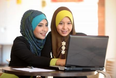 カフェで 2 つのスカーフの女の子使用ラップトップ