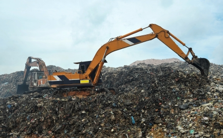 Excavator working in a landfill  Stock Photo