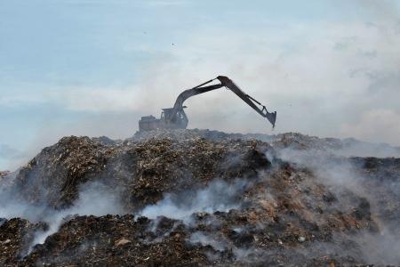 火と煙の埋め立て地ショベル作業 写真素材