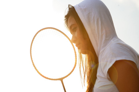 Asian girl hole badminton racket during sunset - flare photo