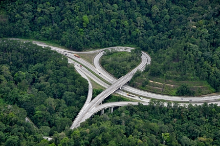 elevated view: Highway interchange in rain forest - Aerial View Stock Photo