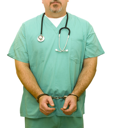 restraints: Medical Fraud - A healthcare professional in handcuffs. Good for medical or insurance fraud concepts. Stock Photo