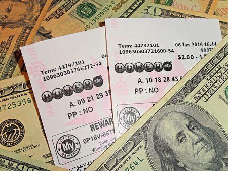 loteria: billetes de lotería Powerball en un fondo de moneda de EE.UU. Editorial