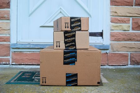 Amazon packages on a front door step 新聞圖片