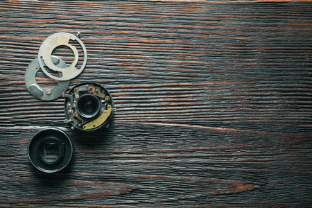 disassembled: Disassembled old lens from old camera on the wooden table Stock Photo