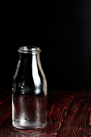 vitreous: Bottle of milk on a black background and wooden table