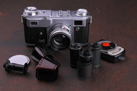 darkroom: Old photo film rolls, cassette and retro camera on wooden background.
