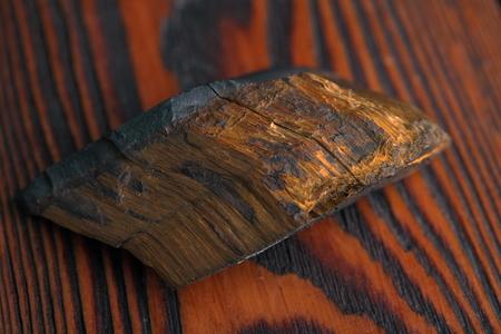 tigers eye mineral on a dark wooden background