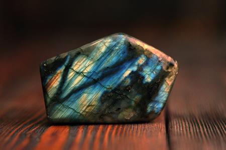 Polished blue labradorite on wooden background Imagens