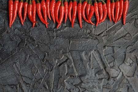Pimienta de chile candente en un fondo negro del cemento. Fondo concreto.
