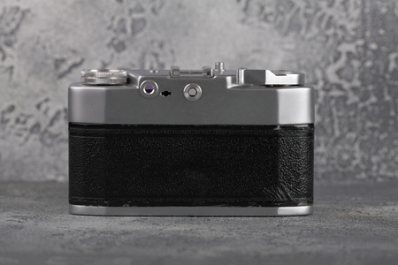 The old rangefinder film camera on a grey cement background.