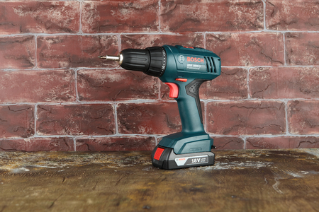 MOSCOW, RUSSIA, AUGUST 18, 2018. 18V Lithium-Ion Cordless Drill/Drivers Bosch GSR 1800-LI on a wooden table against a brick wall.