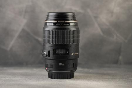 MOSCÚ, RUSIA, 25 DE FEBRERO DE 2019. Lente macro muy popular Canon EF 100 mm f2.8 Lente macro USM sobre un fondo de cemento gris.