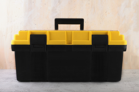 Yellow-black tool box on the background of a concrete wall.
