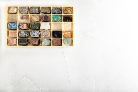 Set of minerals, a collection of rocks, minerals in the box on white cement background. Stock Photo