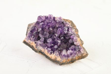 Beautiful amethyst druse close-up on white cement background. Semi precious gem used for jewels.
