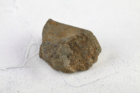Mineral chalcopyrite, copper pyrite from Grekhovskoe, Altai, Russia on white cement background. Copper pyrite composed of iron, copper, and sulfur.