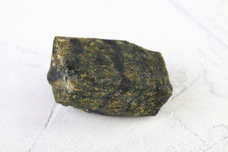 Natural mineral stone - piece of Serpentine, Lizardite gemstone from Bajenovo, Ural, Russia on white cement background.