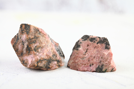 Natural mineral rock specimen - rough rhodonite stone from M. Sidelnikovo, Ural, Russia on white cement background.