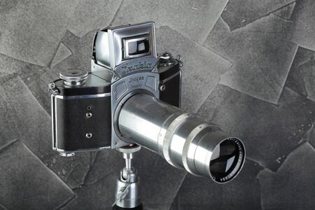 The old German 35 mm SLR film camera Kine Exakta released 1938, with Carl Zeiss lens Triotar 4,0 135 mm lens, released 1942, on a gray cement background.
