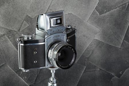 The old German 35 mm SLR film camera Kine Exakta released 1938, with Enna Werk Munhen Lithagon 4,5 35 mm lens, released 1957, on a gray cement background.