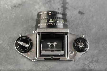 The old 35 mm SLR camera with lens on a grey cement background.