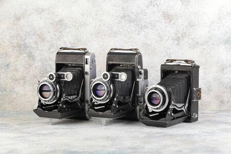 Old medium format rangefinder camera on gray cement background.