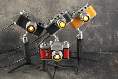 A vintage lamps made by me from an old film cameras on a gray cement background.