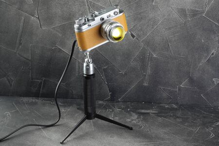 A vintage lamp made by me from an old film camera on a gray cement background. Imagens