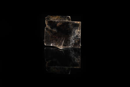 Natural mineral from geological collection - rough muscovite mica, common mica on black glass background.
