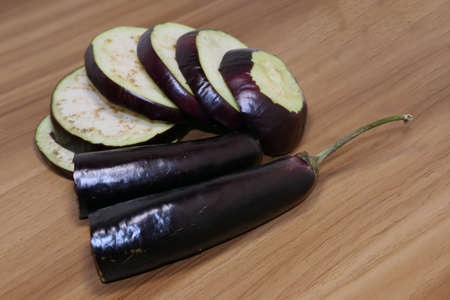 tasty and healthy violet colored Brinjal on wooden table for cooking