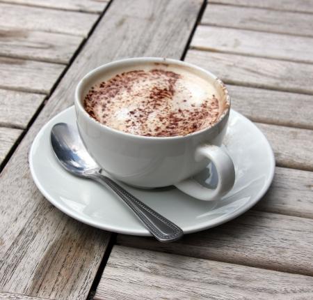 Kopje cappuccino op houten latje tafel met chocolade