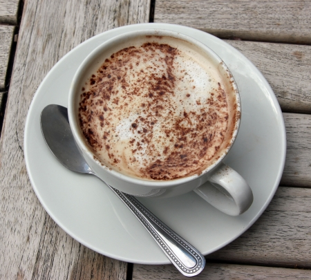 expresso: Cup of Cappuccino on wooden slat table with chocolate