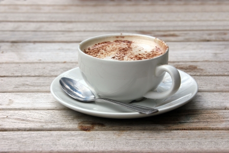 Kopje cappuccino op houten latje tafel met chocolade Stockfoto