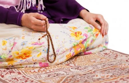 jonge moslim meisje met rozenkrans bidden op een witte achtergrond
