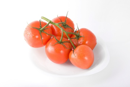 Red ripe tomatoes on plate isolated on white background Stock Photo - 14511355