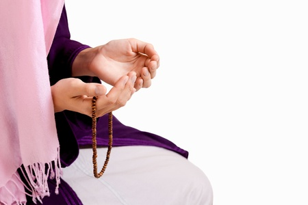 young muslim girl with rosary praying on white background photo
