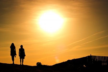 couple of girls walking at sunset