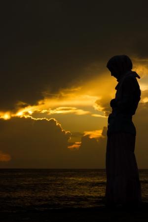mujer rezando: mujer joven musulmán orando al atardecer