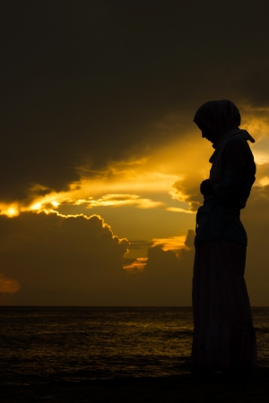 woman praying: young muslim woman praying at sunset Stock Photo