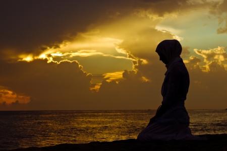 Jonge moslim vrouw te bidden bij zonsondergang Stockfoto - 16097824