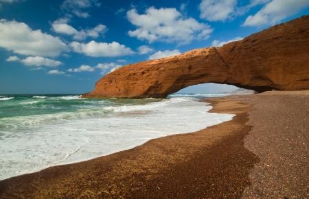 Reusachtige rode kliffen met boog op het strand Legzira Marokko Stockfoto - 16718214