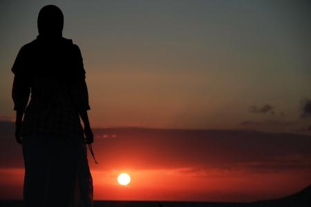 Jonge moslim vrouw bidden met rozenkrans bij zonsondergang