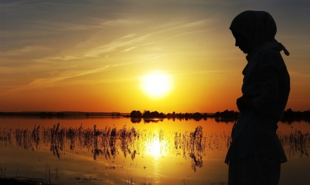 relics: Young muslim woman praying at sunset
