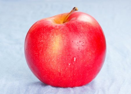 Red ripe apple on blue background Stock Photo - 18850070