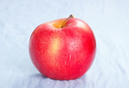 Red ripe apple on blue background Stock Photo - 19549352