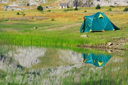 bivouac: Tourist tent stands on the green meadow near the lake